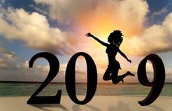 Carte 2019 de bonne année Jeune femme de silhouette sautant sur la plage tropicale au-dessus de la mer et le nombre 2019 avec le  images libres de droits