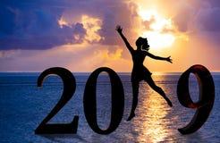 Carte 2019 de bonne année Silhouette de jeune femme sur le support de plage comme partie du signe du numéro 2019 avec le fond de  photos stock