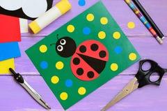 Carte de coccinelle Carte de coccinelle, ciseaux, bâton de colle, crayon, marqueur, ensemble de papier, boussole sur une table en photo stock