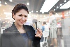 Carte de crédit d'exposition de femme d'affaires avec le contre- service photos stock