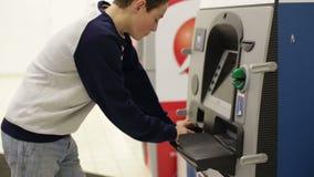 Carte de crédit d'insertion de garçon d'adolescent dans le distributeur automatique de billets clips vidéos
