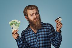 Carte de crédit en plastique de choix sceptique d'homme ou factures de billets de banque d'argent liquide d'argent euro photo libre de droits
