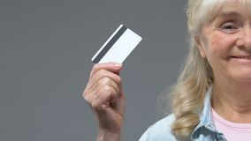 Carte de crédit femelle âgée de sourire d'apparence sur le fond gris, paiement sans argent banque de vidéos