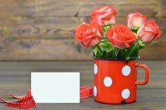 Carte de jour avec les roses rouges dans la tasse de vintage Image stock