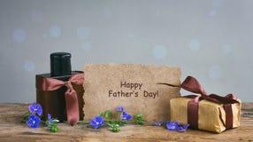 Carte de jour de pères, boîte-cadeau avec le ruban brun, bouteille de parfum, PA images libres de droits