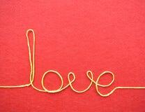 Carte de jour de valentines - amour fait à partir du fil sur le fond rouge Photographie stock libre de droits