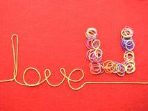 Carte de jour de valentines - amour fait à partir du fil sur le fond rouge Image stock