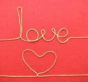 Carte de jour de valentines - coeur fait à partir du fil sur le fond rouge Image libre de droits
