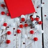 Carte de jour du ` s de Valentine avec de petits coeurs et sucrerie blanche rouge Photographie stock