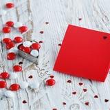 Carte de jour du ` s de Valentine avec de petits coeurs et sucrerie blanche rouge Photographie stock libre de droits