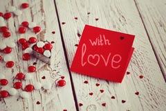 Carte de jour du ` s de Valentine avec de petits coeurs et sucrerie blanche rouge tonalité de l'image Images stock