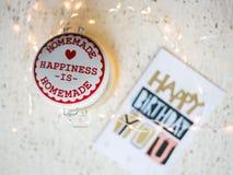Carte de joyeux anniversaire sur une table et des lumières de Noël Image stock