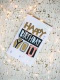 Carte de joyeux anniversaire sur une table et des lumières de Noël Images libres de droits