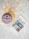 Carte de joyeux anniversaire sur une table et des lumières de Noël Images stock