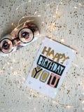 Carte de joyeux anniversaire sur une table et des lumières de Noël Image libre de droits