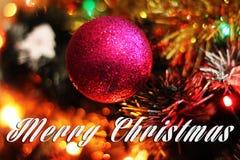 Carte de Joyeux Noël avec la boule rouge et le fond coloré de bokeh Photos libres de droits