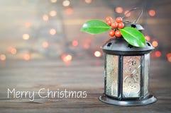 Carte de Joyeux Noël avec la lanterne de Noël et le houx de Noël photographie stock libre de droits
