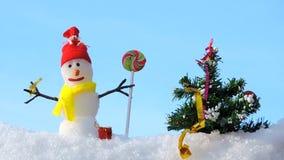 Carte de Joyeux Noël, bonhomme de neige avec l'arbre de Noël en parc d'hiver, salutation de Noël banque de vidéos