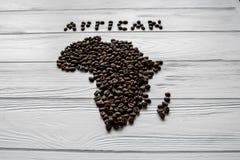 Carte de l'Afrique faite de grains de café rôtis s'étendant sur le fond texturisé en bois blanc Photos libres de droits
