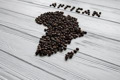 Carte de l'Afrique faite de grains de café rôtis s'étendant sur le fond texturisé en bois blanc Images stock
