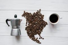 Carte de l'Amérique du Nord faite de grains de café rôtis s'étendant sur le fond texturisé en bois blanc avec la tasse de café, f Photos stock