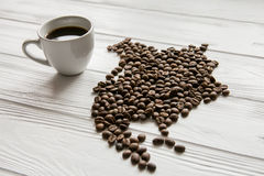 Carte de l'Amérique du Nord faite de grains de café rôtis s'étendant sur le fond texturisé en bois blanc avec la tasse de café Image stock