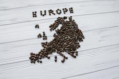 Carte de l'Europe faite de grains de café rôtis s'étendant sur le fond texturisé en bois blanc Photos libres de droits