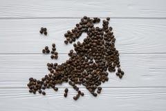 Carte de l'Europe faite de grains de café rôtis s'étendant sur le fond texturisé en bois blanc Photo libre de droits