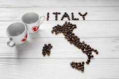 Carte de l'Italie faite de grains de café rôtis s'étendant sur le fond texturisé en bois blanc avec deux tasses de café Photo stock