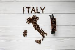 Carte de l'Italie faite de grains de café rôtis s'étendant sur le fond texturisé en bois blanc avec le train de jouet Photo stock