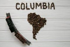 Carte de la Colombie faite de grains de café rôtis s'étendant sur le fond texturisé en bois blanc avec le train de jouet Photo stock