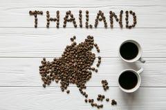 Carte de la Thaïlande faite de grains de café rôtis s'étendant sur le fond texturisé en bois blanc avec deux tasses de café Photo stock