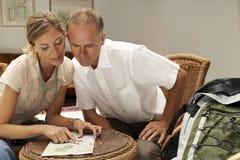 Carte de lecture de couples à la maison Photos stock