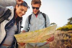 Carte de lecture de couples sur la promenade de pays Photo stock