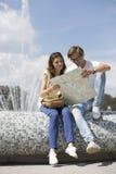 Carte de lecture de couples tout en se reposant sur la fontaine Image libre de droits