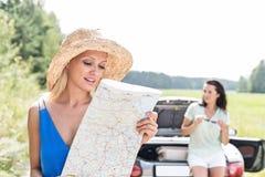 Carte de lecture de femme tandis qu'ami se penchant sur le convertible à l'arrière-plan Image stock
