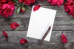 Carte de livre blanc avec le crayon en bois, les pivoines roses et les pétales sur le fond en bois rustique Image stock