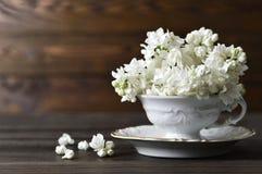 Carte de mariage : Fleurs lilas blanches dans la tasse de vintage Photographie stock libre de droits
