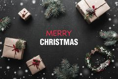 Carte de Noël Avec l'espace de message de félicitations pour aimé Cadeaux qui attendent des enfants entre les branches du sapin Image libre de droits