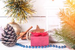 Carte de Noël avec la branche de lueur d'une bougie, de boîte-cadeau et de sapin sur le fond en bois images libres de droits