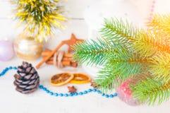 Carte de Noël avec la lueur d'une bougie, la cannelle et la branche de sapin sur le fond en bois image libre de droits