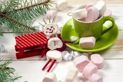 Carte de Noël avec le bonhomme de neige de guimauve d'amusement dans la tasse verte, arbre Image stock
