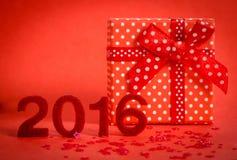 Carte de Noël 2016 avec le grand boîte-cadeau sur le rouge Photographie stock libre de droits