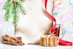 Carte de Noël avec le thé, les biscuits et la cannelle Photographie stock libre de droits