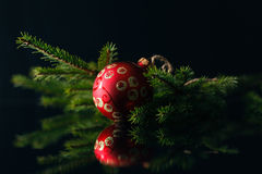 Carte de Noël avec les babioles rouges et arbre de fourrure sur le fond noir Photos stock
