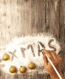 Carte de Noël avec une main femelle écrivant Noël, boules d'or dans la neige sur un fond en bois Photo libre de droits