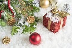 Carte de Noël Branche de pin, cadeau rouge, décoration sur un fond de neige Images libres de droits