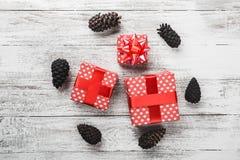 Carte de Noël, cadeau enveloppé dans l'emballage rouge avec les cônes décoratifs colorés de pin Photos libres de droits