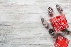 Carte de Noël, cadeau enveloppé dans l'emballage rouge avec les cônes décoratifs colorés de pin, fond blanc avec les cadeaux mode Photo libre de droits