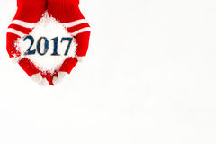 Carte de Noël, gants sur des mains tenant la neige et 2017 nouvelles années i Photographie stock libre de droits